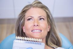 Extreme close up doctor holding tooth whitening equipment by smiling patient royalty free stock photos