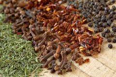 Extreme close up of dried herbs and spices on a wooden cutting board. Macro shot of ground savory, clove, paprika and pepppercorn Royalty Free Stock Photography