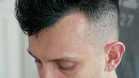 Extreme close up face of man in hairdressing salon. Barber cuts hair by clipper. Extreme close up shot of face of man in hairdressing salon during haircut stock video