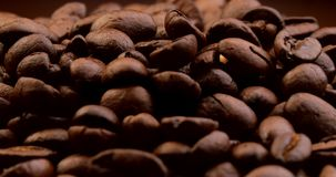 Extreme close-up of falling coffee beans. Extreme close-up of roasted arabica coffee beans falling down and filling the frame stock footage