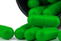 Generic Green Pills. Image showing a very close view of a green supplement or medicine pills, in capsule form, falling out of an open bottle royalty free stock image