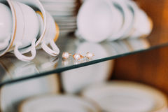 Extreme close-up gold jewelry embellished with pearls on glass cupboard shelf. Porcellain cups and plates at background.  Stock Photography