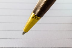 Extreme close up of gold pen. And paper Stock Image