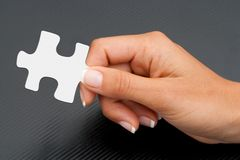 Extreme close up of hand holding puzzle piece. Royalty Free Stock Photos