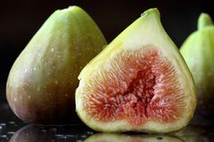 Extreme close up of the inside of a fig. Two and a half sliced fresh fig fruits on a black background with reflections and waterdr Stock Photography