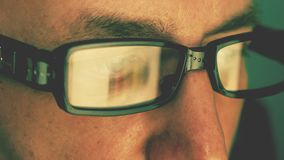 Extreme close up man face eyes glasses. Reflection from computer laptop screen in fashion glasses. Caucasian white man stock footage