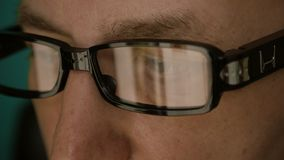 Extreme close up man face eyes glasses. Reflection from computer laptop screen in fashion glasses. Caucasian white man stock video