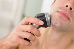 Extreme Close up of man shaving with electric razor Royalty Free Stock Photo