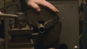Technician use vernier calliper, Africa Mercy. Extreme close up pan shot, old , rusty, grey painted lathe machine is switched on, machining, a shaft gear held in stock video footage