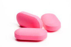 Extreme close-up of pink pills isolated on white Stock Image