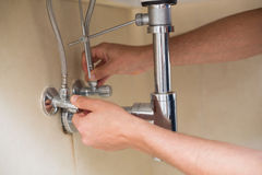 Extreme Close up of a plumber's hands and washbasin drain Stock Images