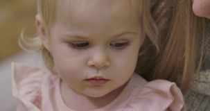 Extreme close-up of sad little Caucasian girl looking down. Portrait of cute gloomy child with beautiful grey eyes and stock video footage