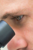Extreme Close up of a scientific researcher using microscope Royalty Free Stock Photo