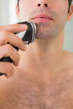 Extreme Close up of shirtless man shaving with electric razor Stock Photos