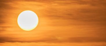 Extreme close up of the sun setting with dramatic red clouds at sunset. Pamoramic image. stock photography
