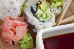 Extreme Close Up on Sushi and Garnish. Sushi Rolls with regular garnishes of wasabi, ginger, and soy sauce viewed in extreme detail Royalty Free Stock Images
