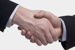 Extreme close up of two Businessmen shaking hands, studio shot Stock Images