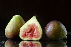 Extreme close up of two and a half sliced fresh fig fruits on a black background with reflections and waterdrops. Macro food textu Stock Photo