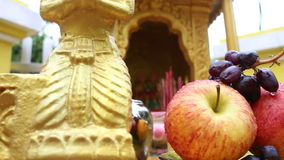 Extreme close up of various fruit being offered at a local spirit house in So. Utheast Asia; camera moves to reveal gold figure on the left, then figure on the stock video footage