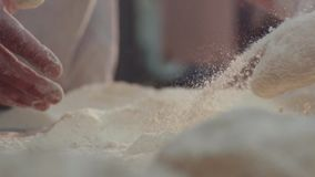 Extreme close up view of baker's hands one by one kneading the pieces of dough in the flour on the table. Beautiful