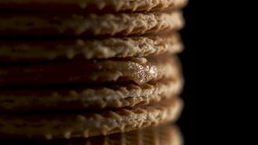 Extreme close up view on traditional Dutch and Holland stroopwafels rotate or spin on a black mirror on a black