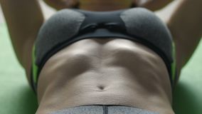 Close-up woman doing crunches on exercise mat. Extreme close-up of woman in sports top doing crunches on exercise mat. Young female working out doing abdominal stock video