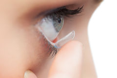 Extreme close up on young model applying contact lens Royalty Free Stock Photo