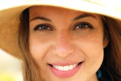 Extreme close up of young model face with straw hat smiling at camera under summer rays sun on the beach. royalty free stock image
