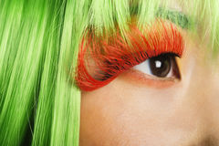 Extreme close-up of young woman's face with false eyelashes and green wig Royalty Free Stock Photo