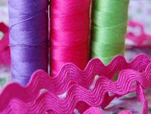 Extreme closeup of colorful spools of thread in purple, pink and green stock images