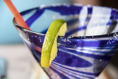 Extreme closeup of lip of swirly blue margarita class with lime and salt on rim - selective focus royalty free stock photography