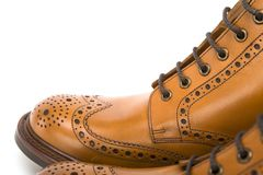 Extreme Closeup of Mens Tanned Brogue Leather Boots with Rubber Sole Royalty Free Stock Image