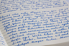 Extreme closeup of open notebook with handwritten lorem ipsum t. Ext on a ruled paper stock image