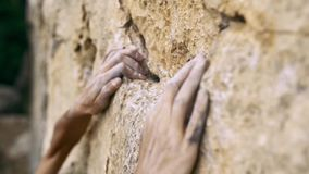 Extreme closeup orange limestone cliff and woman`s hands reaching and holding holds.