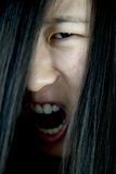 Extreme closeup of scary asian monster zombie face shouting Stock Photography