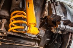 Yellow shock absorber underneath a car. Extreme closeup of yellow shock absorber underneath a car royalty free stock images