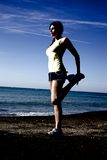 Extreme contrast of woman stretching leg in front of the ocean Royalty Free Stock Images