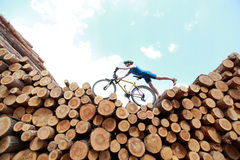 Extreme cycling. Fit man with his bicycle on top of large pile of logs royalty free stock image