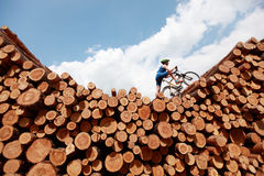Extreme cycling. Fit man with his bicycle on top of large pile of logs stock photo