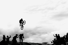 Extreme cyclists, young man doing jump with bmx bike on background of black and white silhouette and clouds Royalty Free Stock Photos