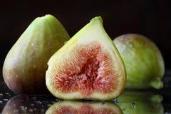 Extreme dichte omhooggaand van de binnenkant van fig. Twee en een half gesneden verse fig.vruchten op een zwarte achtergrond met  Stock Foto
