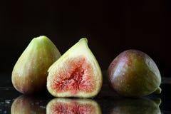 Extreme dichte omhooggaand van twee en een half gesneden verse fig.vruchten op een zwarte achtergrond met bezinningen en waterdro Stock Foto