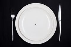 Extreme diet. Concept of extreme diet. Dish with only a grain of pepper on it Royalty Free Stock Images