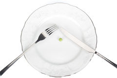 Extreme dieting. Single pea on a plate over white background Royalty Free Stock Photos