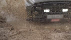 Extreme driving conditions in the countryside. A powerful SUV drives into a deep puddle. Flying splashes and dirt stock footage
