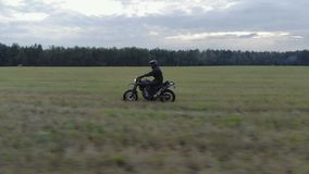 Extreme driving a motorcycle on rough terrain. Aerial shot extreme driving Enduro over rough terrain. A man in black protective gear controls a motorcycle riding stock footage
