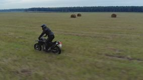 Extreme driving a motorcycle on rough terrain. Aerial view extreme driving over rough terrain. Man in black protective gear standing controls motorcycle stock video
