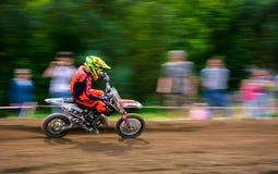 Extreme enduro MOTO SPORT for kids. Uzhgorod, Ukraine - May 21, 2017: Junior MX rider turns on a corner. Motion blur with flying dirt. TransCarpathian regional Royalty Free Stock Photo