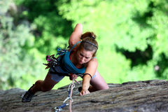 Extreme female climber. A concentrate female rock climber claiming a stone wall on a green forest   background Stock Photo