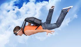 Extreme flight man with a parachute in the clouds. Background Stock Photo
